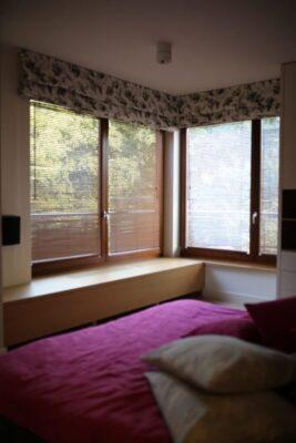 Odsłonięte drewniane żaluzje w sypialni