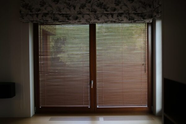 Zamknięte żaluzje drewniane umieszczone na drzwiach tarasowych